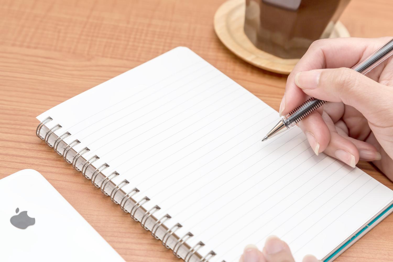 カフェでノートに記入する手